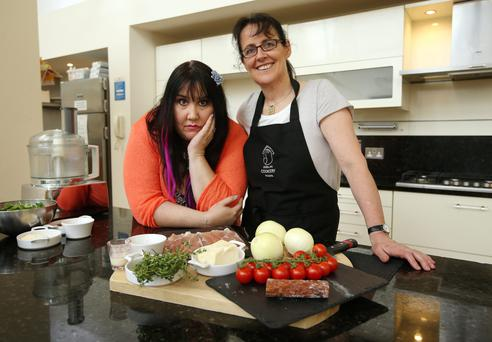 Andrea Smith pictured with Professional Chef Lynda Booth and some of the ingrediants for her meal at the Dublin Cookery School in Blackrock.