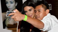 Selfless: Kim Kardashian poses for a selfie with a fan