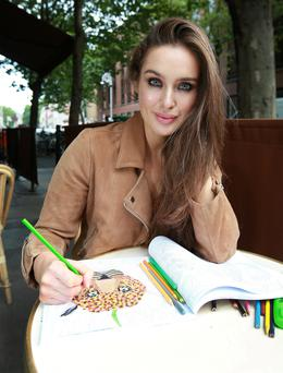 Model Roz Purcell chills with her colouring book on Dublin's Dawson Street. Photo: Frank Mc Grath