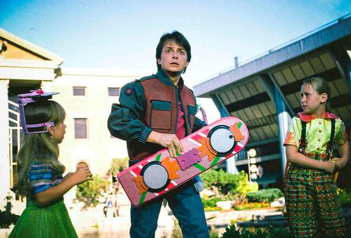Michael J Fox as Marty McFly in Back to the Future II, holding his hoverboard.