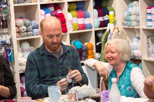 Knitty gritty: Marina Hand, owner of Winnie's Craft Cafe in Booterstown, teaches Eoin Butler how to start a line during his first knitting circle visit. Photo: El Keegan.
