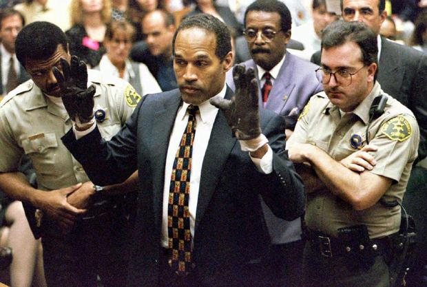 Sensational: OJ Simpson holds up his hands to the jury wearing the infamous gloves found during his 1995 murder trial.