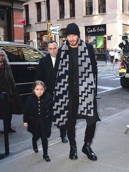 Pro: Harper Beckham, 4, with dad David, attends mum Victoria's NYFW show this week.