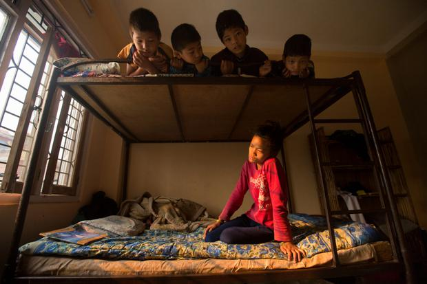 Agunita Tamang in the bottom bunk-bed and four boys above including Sureju Maiia, Krisuna Buda and Dil Buda, who were found after the earthquake, at an Umbrella home in Nuwakot. Photo: Mark Condren