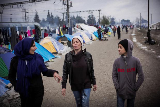 Two women walking through the camp at Idomeni.