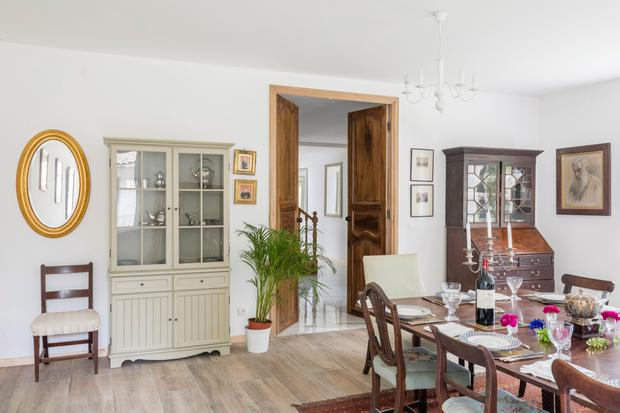 The dining room is furnished mainly with antiques. When Nell and Joe bought the house, they raised the ceilings and put in new floors. The wood-effect flooring is actually ceramic tiling. The portrait is that of Nell's great grandfather.