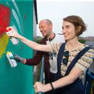 Art class: James Earley teaches Kirsty Blake Knox how to use a spray can. Photo: Patrick Browne