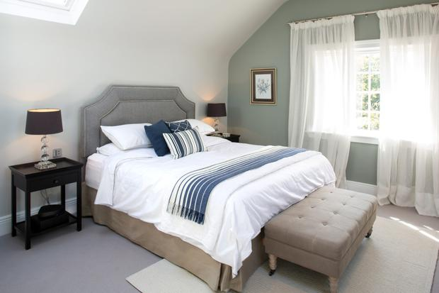 The master bedroom is furnished in a mix of antique and contemporary furniture. The Neptune headboard is in Elliot wool