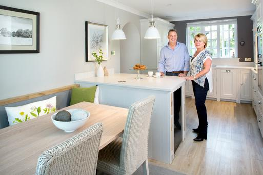 Martin and Colette in the kitchen, which is by Neptune. The space was quite limited, so they opted for a peninsula - rather than an island - and it houses a wine fridge. The countertops are made of Caesarstone and the chairs are Lloyd Loom style