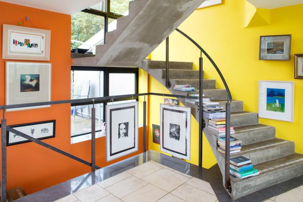 The staircase, which is made of poured concrete, is lined with books, and the colourful walls are hung with the works of local artists and that of Damien's cousin, Gwen O'Dowd