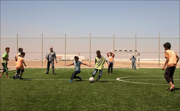 Liam plays football with children in Azraq camp. Photo: David Conachy