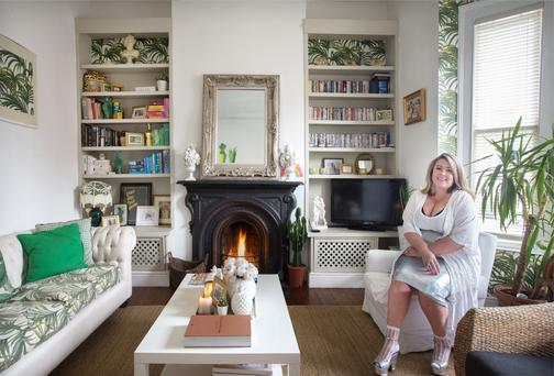 Andrea Horan in the living room, which is furnished with lots of her favourite plants, ferns - real, fabric and paper
