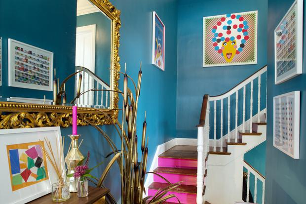 The vibrancy of the blue hallway with its pink stairs is tempered by touches of gold. Andrea is a fan of Damien Hirst and has several of his prints.