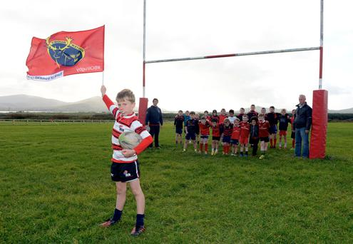 Shoulder to shoulder: Harry Curran waves the Munster flag in front of trainers Gary Curran and Mike Lyne and some of the young members of Dingle Rugby Club at their pitch in Corrig, West Kerry. Photo: Don MacMonagle