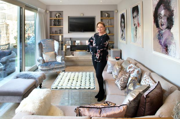 Norah in her living area with some of her favourite pieces, including the perspex coffee table embedded with white roses. She also loves the upholstered chair covered in copper-embossed velvet by textile designer Aoife Mullane
