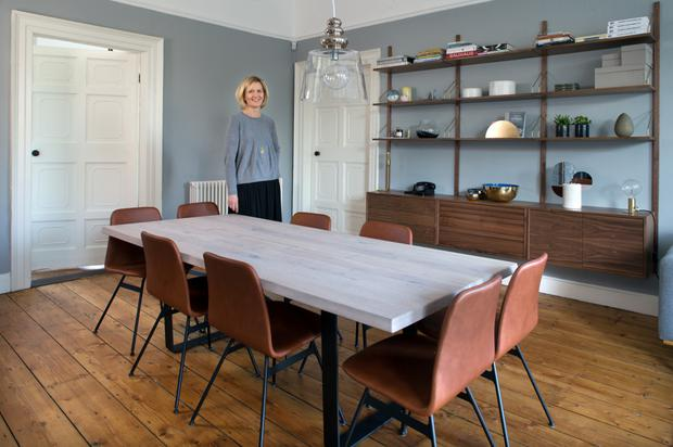 Helle in her dining area. The shelving is by Danish designer Poul Cadovius. Dating from 1948, it's known as the Royal system, and is one of the world's first modular systems. The table, which has two extra leaves, is by DK3 as are the tan leather chairs
