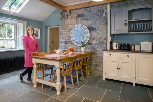 Fiona in the kitchen, which was originally a shed. The stone wall is the outside wall of the original house. They installed new flagstones and windows. Photo: Tony Gavin