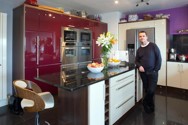 Aengus in the kitchen with its purple units and black granite worktops. He loves to cook for himself, his husband, Terry, and their friends so he opted to put in two ovens, two warming drawers and two microwaves.