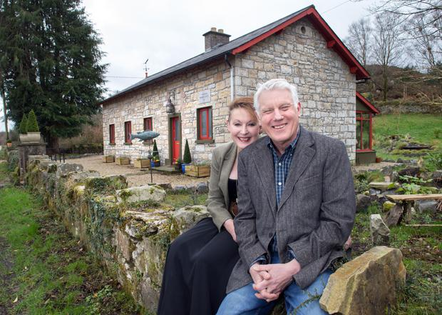 Jane and Brian Wright outside their home - the stone schoolhouse where an Irish hero began his education. The fish was made by David Ferro, famous in the States for his weathervanes
