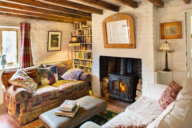 The living room is in the adjoining cottage. Deirdre had the plaster taken off the walls and the beams exposed to give a more rustic look. She added the stove and the bookshelves