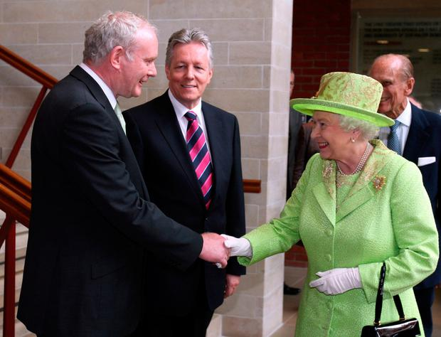Queen Elizabeth shakes hands with Deputy First Minister of Northern Ireland Martin McGuinness watched by First Minister Peter Robinson (centre) in Belfast in 2012