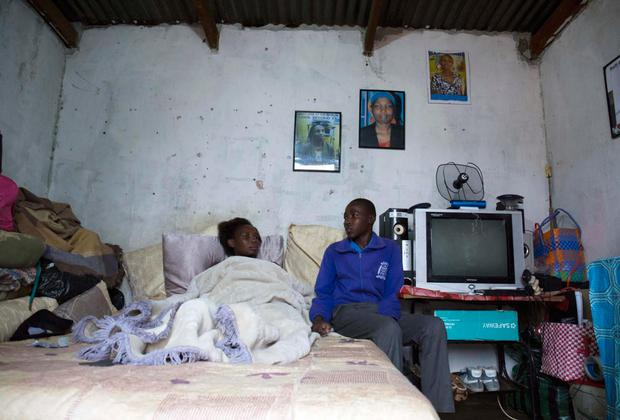 Simphiwe and his mother Girlie, who both have HIV, in their tiny home on the outskirts of the city of Manzini. Photo: Clare Keogh