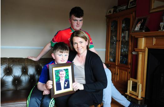 Raw pain: Patricia Gibbons and her sons Connor (15) and David (8) with a picture of James, at their home in Rahan, Co Offaly. Photo: James Flynn/APX