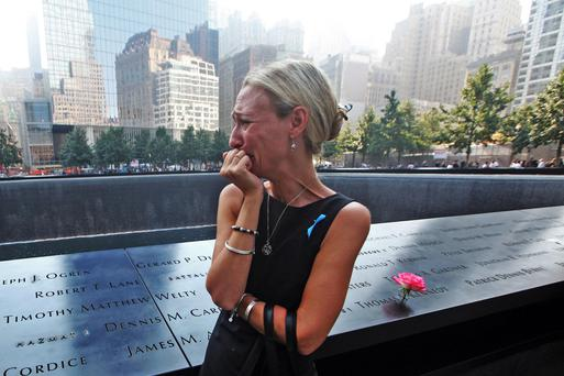 Remembered: Carrie Bergonia looks over the name of her fiance, firefighter Joseph Ogren, at the 9/11 Memorial on the anniversary of the attacks. Photo: Chris Pedota