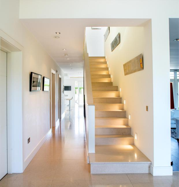 Light pours in from all over the house to create a light-filled hallway. The stairs is Portuguese limestone