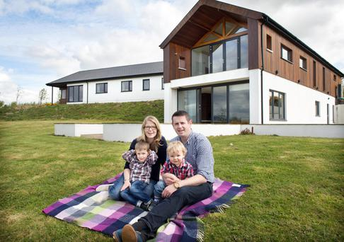 David and Christine with their two boys Eoghan, (four) and Ben, (16 months), outside their home in the Wexford countryside. The house, designed by architect Fergus Flanagan, is single storey to the front, while the two-storey back has massive amounts of glazing to afford wonderful views of Mount Leinster