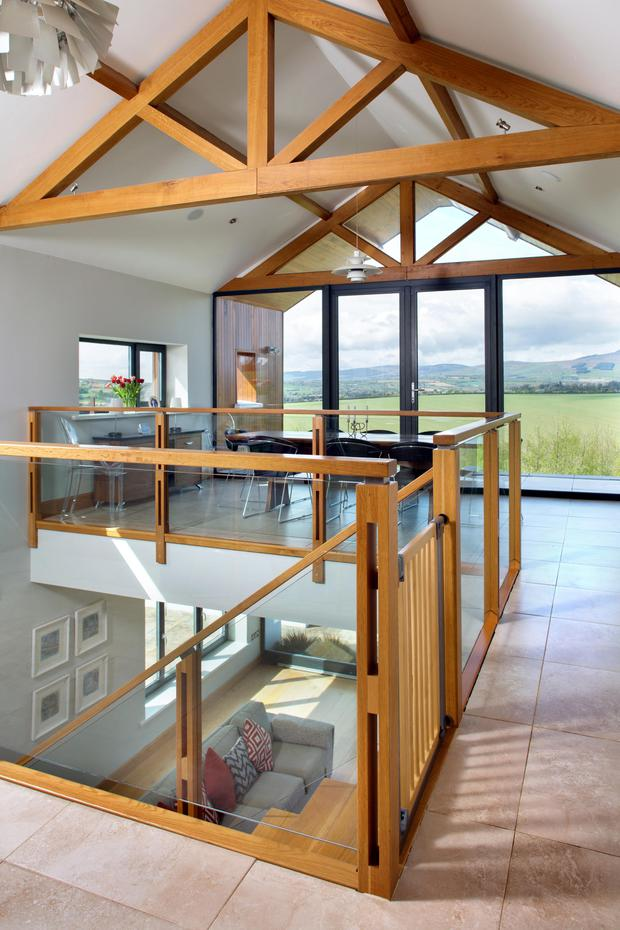 The contemporary glass-and-wood staircase is between the kitchen and the dining area and links the two floors. The floor is ceramic, while the roof beams are made of French oak
