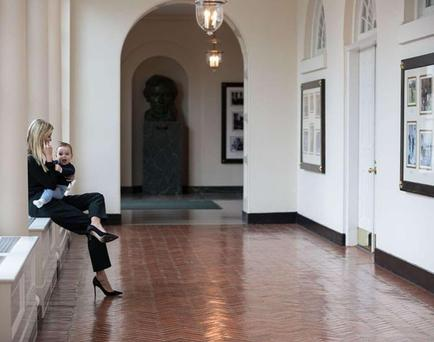 Ivanka juggling work with her son on her knee