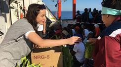 Helping hand: Katie Byrne hands out supplies to migrants on board MSF Aquarius