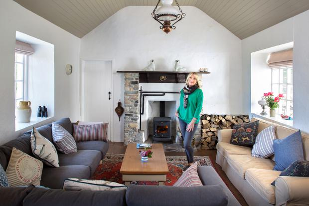 Alix in the cosy livingroom with its original fireplace. Recently, the family installed the wood-burning stove, but they retained the other original elements, including the fire crane for cooking. The sofas are from Ikea, while the Persian rug is an antique