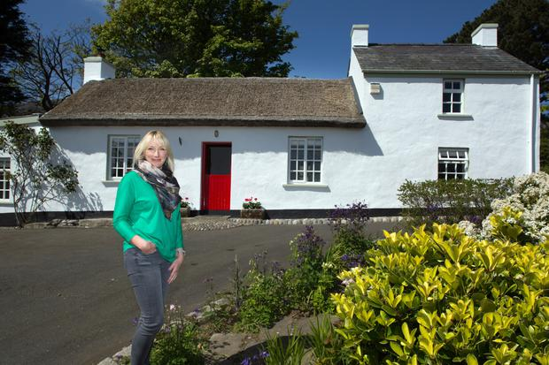 Alix Mulholland outside her family's holiday home in the Mourne Mountains. Over 250 years old, it was originally a coach stop and inn. Alix's parents bought it in 1976 and completely restored it, retaining all its original features including the half door. The thatch has to be repaired every 10 years and completely redone every 20 years