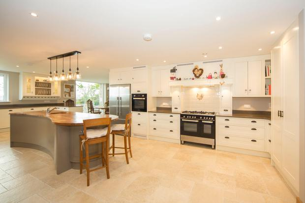 The kitchen is the heart of the modern new home, built alongside the original thatched cottage, which has been renovated