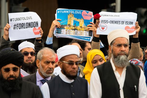 British imams and other religious leaders and other religious leaders hold up signs with hashtags to show the internet can be a force for good during another vigil in the UK capital. Photo: Dominic Lipinski/PA