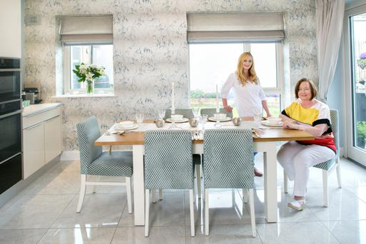 Interior architect Lorna Kee and her mother in Cora's new light-filled dining area. The back is north-facing but still gets a lot of sun as the house is a bungalow.The tiles are porcelain, the wallpaper is by Harlequin and the geometric-patterned fabric on the chairs is by Romo