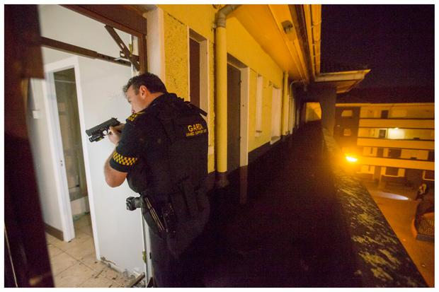Sgt Tallon during a raid on an apartment. Photo: Mark Condren