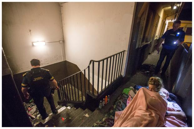 A homeless woman is awoken during a raid by the Armed Response Unit of An Garda Siochana. Photo: Mark Condren