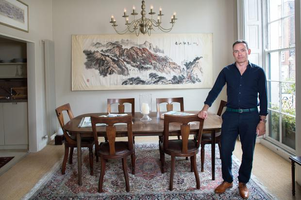 Eugene in the dining area of his apartment. The compact kitchen is just off it. The dining table is mid-century modern, and the chairs, which belonged to his grandfather, are late 19th Century.