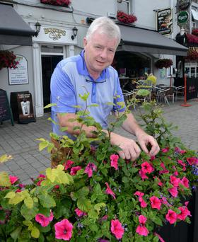 Publican Ger Counihan tending to flowers outside his pub Bunkers Bar in Killorglin, Co Kerry. Photo: Don MacMonagle