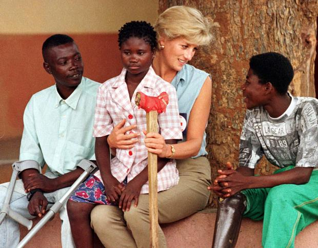 Diana, after finding a new role for herself, holding an Angolan amputee child on her lap in Luanda in January 1997 during a visit to help a Red Cross campaign outlaw landmines worldwide