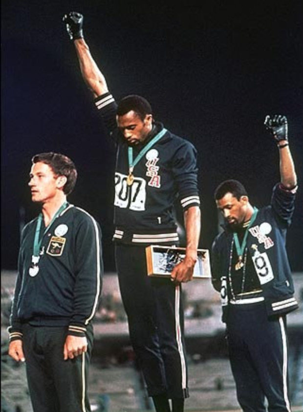 It is one of the defining images of sport and protest of the 20th century - two black American athletes, Smith and Carlos, stand on the medal podium at the Olympics, their fists raised in the Black Power salute, protesting racism in their homeland. Both athletes suffered severe repercussions for their act.