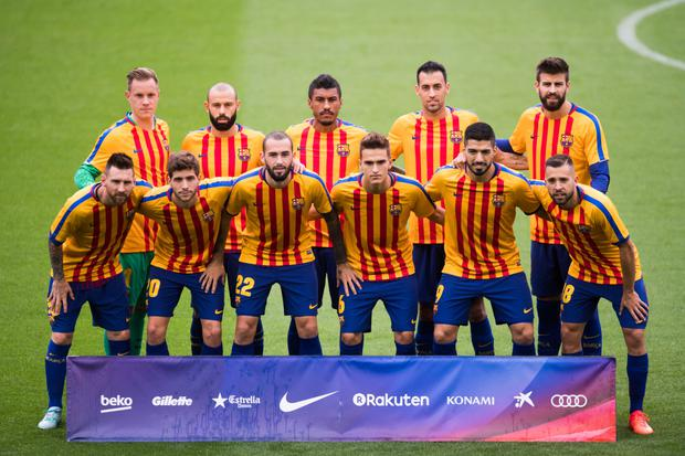 Players of FC Barcelona pose for a team photo wearing shirts in the colours of the Catalan flag, prior to kickoff against Las Palmas at Camp Nou on Sunday