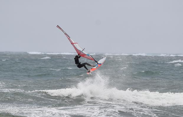 Pier pressure: A windsurfer battles the waves off the Kerry coast on Monday