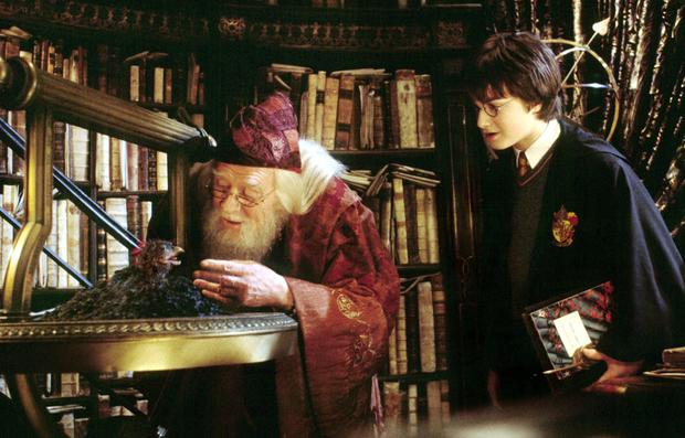 Daniel Radcliffe (R) stars as Harry Potter as he watches as Professor Dumbledore, portrayed by the late Richard Harris, feed Fawkes the Phoenix