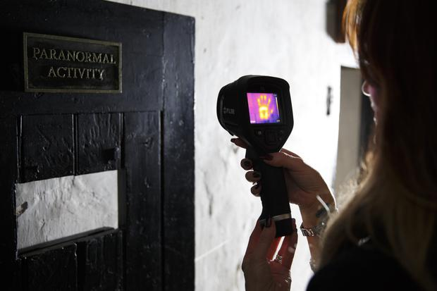 One of the team uses a thermal imager on a cell door