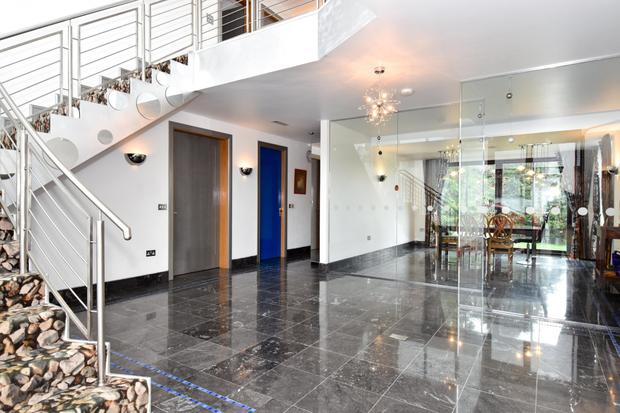 The black marble-floored atrium-style entrance hall with its dramatic staircase