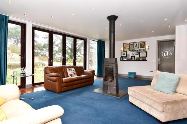 The family room with central solid-fuel stove and wall-to-floor windows